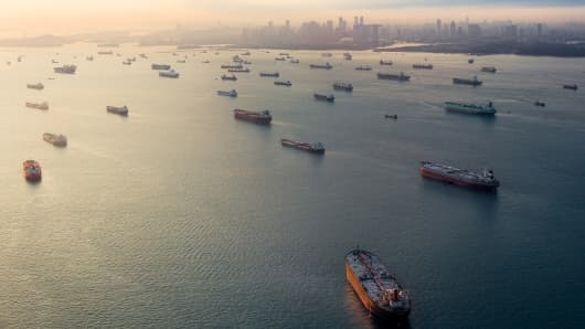 Cargo ships sit idle in the Singapore Strait as the sun sets over a hazy Singapore skyline.