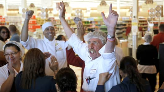 Market Basket meat manager Bob Dietz, raises his arms in celebration after watching a televised speech by restored CEO Arthur T. Demoulas, Thursday, Aug. 28, 2014, in Chelsea.