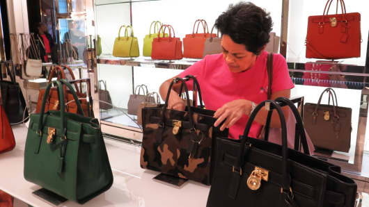 A shopper looks at Michael Kors handbags at Macy's flagship store in New York.