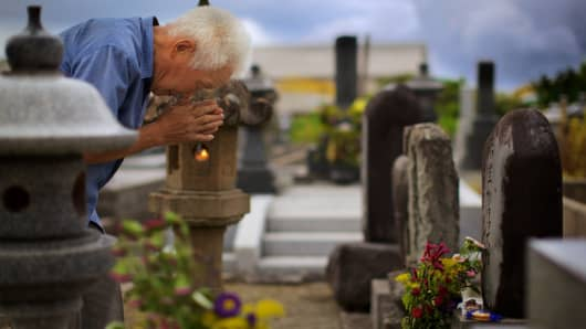 During the 'Obon' festival in Japan, an old man pays respects to his ancestors at a local neighborhood cemetery.