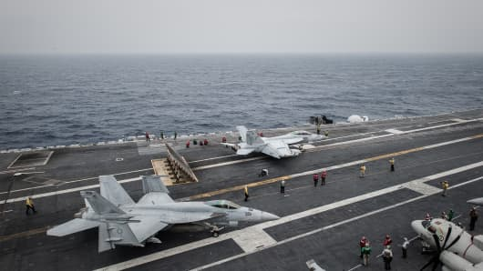 A pair of US Navy Boeing F/A-18 Super Hornet aircraft prepare for a catapult launch from the flight deck of the US nuclear-powered aircraft carrier USS George Washington off the coast of Hong Kong.