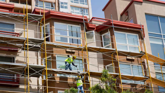 Contractors work on construction of a new apartment building in downtown Seattle.