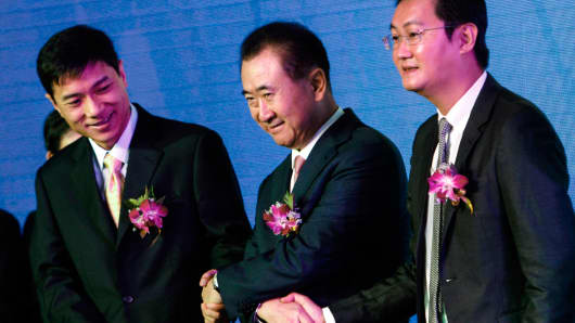 Wang Jianlin (C), Chairman of Wanda, holds hands with Tencent Chief Executive Officer Pony Ma (R) and Baidu Inc. Chairman and CEO Robin Li (L), in Shenzhen, Guangdong province, August 29, 2014.