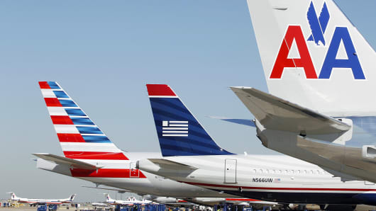 The tail sections of American Airlines aircraft and a US Airways aircraft at the Dallas/Fort Worth International Airport.