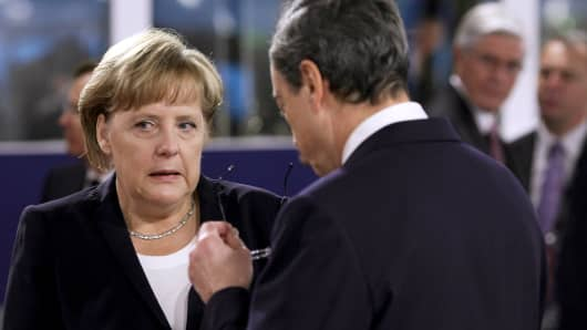 German Chancellor Angela Merkel speaks with Mario Draghi, president of the European Central Bank (ECB).