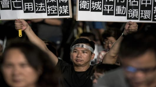 A protester holds placards at a pro-democracy rally next to the Hong Kong government complex on August 31, 2014.