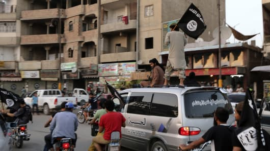 Members loyal to the Islamic State in Iraq and the Levant (ISIL) wave ISIL flags as they drive around Raqqa June 29, 2014.