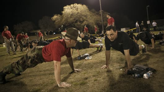Former Army Drill Sergeant Hector Mallen, left, motivates Jose Fernandez, a USAA employee, as he does push-ups during the company's Zero Day PT, which gives employees a taste of military life, in San Antonio, March 21, 2014.