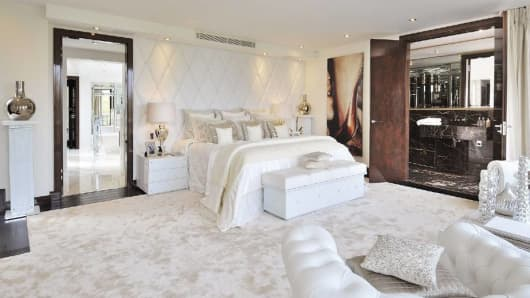 The master bedroom, with its all-white interior, was created to be a soothing retreat. The carpet is silk and the leather headboard has Swarovski crystal detail.