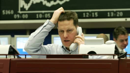 A trader sitting in front of a chart displaying German share index DAX.