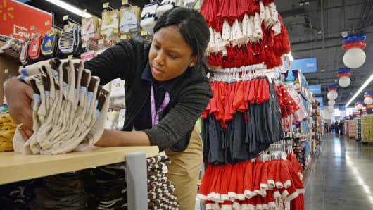 A Walmart employee checks prices on merchandise before the opening of a new store in Washington.
