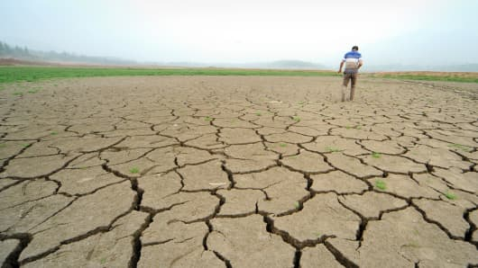 A farmer walks over dried and cracked earth that used to be the bottom of Zhifang Reservoir on July 29, 2014 in Dengfeng, China.