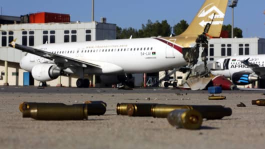 Bullet casing and damaged airplanes on the tarmac at Tripoli international airport after fighters from the Libyan Dawn coalition captured the airport from allies of rogue general Khalifa Haftar.