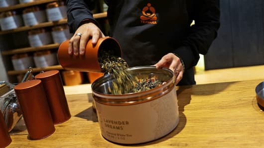 An employee pours tealeaves at the newly opened Teavana tea bar in New York.