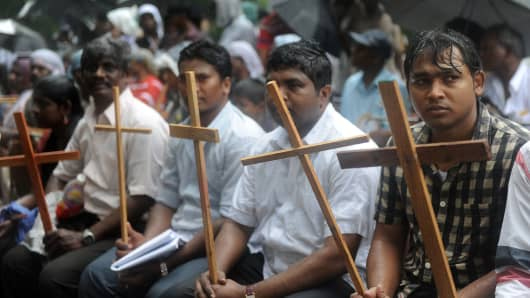 Christians and Muslims sit in the rain during a protest rally in New Delhi on August 1, 2012.