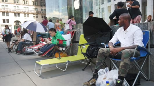 People sit in front of an Apple store in New York on September 4, 2014.