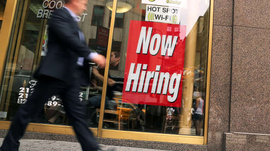 "A ""now hiring"" sign at a fast-food restaurant in New York"