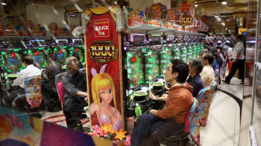 Customers play pachinko machines in a pachinko parlor in Tokyo, Japan.