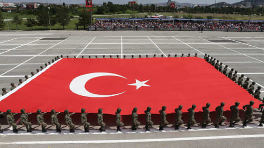 Turkish soldiers parade with a large Turkish national flag on August 30, 2014 in Ankara.