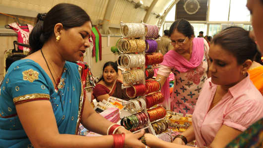 Women purchase bangles during Teej festival at Dilli Haat in New Delhi, India.