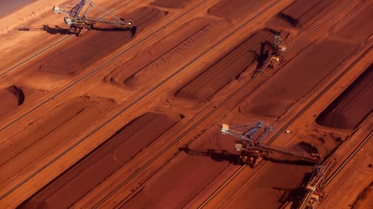 Stackers load crushed iron ore onto a stockpile at an ore processing facility in Pilbara, Western Australia.