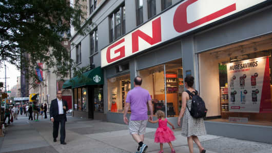 Pedestrians walk by a GNC store in New York.