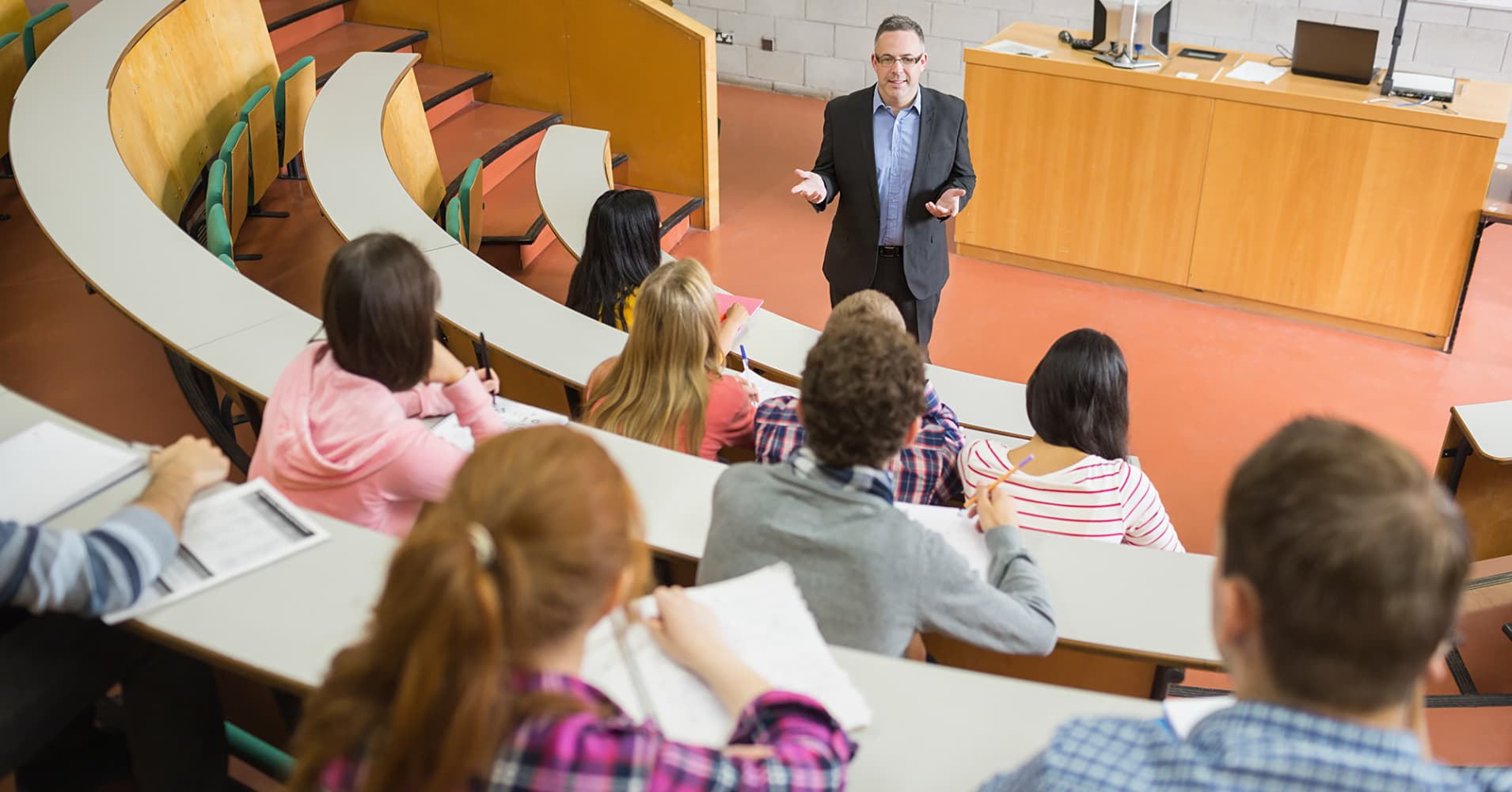 Teacher speaking to students in lecture hall