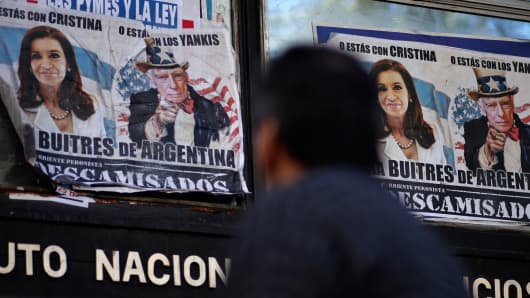 A man walks past posters with pictures of Argentina's President Cristina Fernandez de Kirchner and U.S. District Court for the Southern District of New York Judge Thomas Griesa, depicted as Uncle Sam, near the Argentine Congress in Buenos Aires, September 10, 2014.