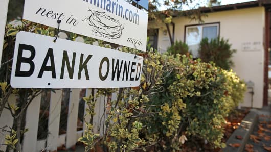"A ""bank owned"" sign that is posted in front of a home for sale in San Rafael, Calif."