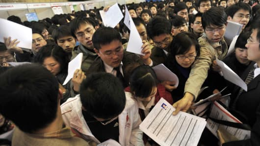 A group of jobseekers rush to put in their applications as thousands of unemployed Chinese graduates flock to a job fair in Wuhan, central China's Hubei province.