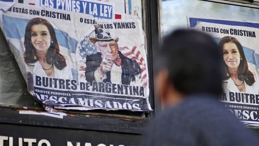 A man walks past posters with pictures of Argentina's President Cristina Fernandez de Ki