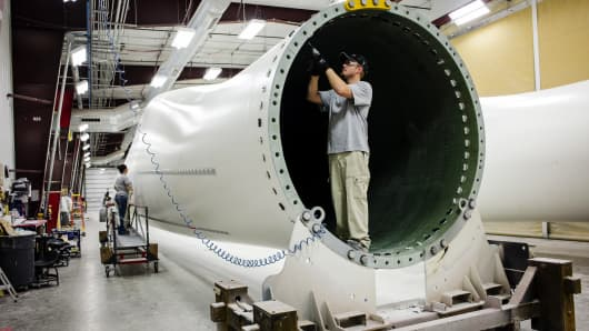 A worker installs components at the base of a wind turbine blade at the Siemens AG turbine blade plant in Fort Madison, Iowa.