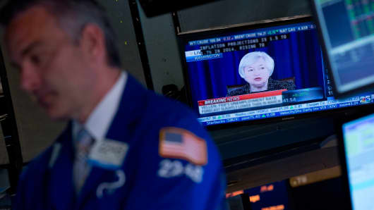 A trader works on the floor of the NYSE as Fed Chair Janet Yellen speaks on television during a June news conference.