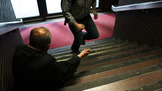 A man begs for money on a stairwell in an entrance to the Port Authority Bus Terminal in New York City.