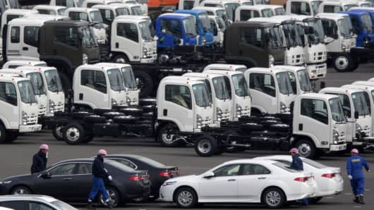 Vehicles bound for shipment sit in a lot at a port in Yokohama, Japan