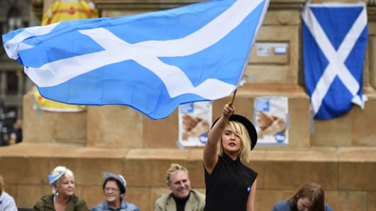 A woman waves a Scottish Saltire at a 'Yes' campaign rally in Glasgow, Scotland September 17, 2014. The referendum on Scottish independence will take place on September 18, when Scotland will vote whether or not to end the 307-year-old union with the rest of the United Kingdom.