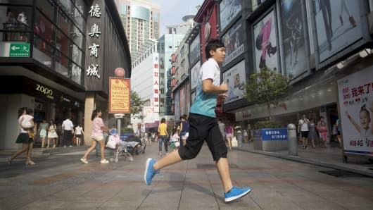 A man runs across a street in the pedestrianized Dongmen area of Shenzhen, China, on Monday, Aug. 4, 2014.
