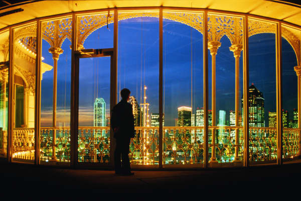 The Dallas skyline seen through the windows of a penthouse at night.