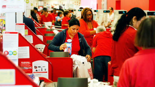 Retail employees help customers at the checkout registers inside a store  in Torrance, California.