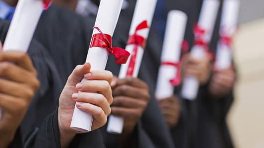 College students hold diplomas at graduation