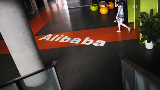 An employee walks past the Alibaba logo during a media tour organized by government officials at the company's headquarters on the outskirts of Hangzhou, Zhejiang province, China.
