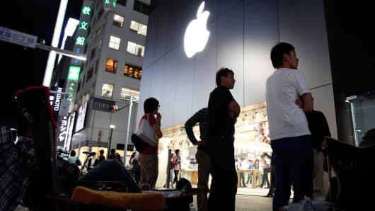 People wait for the release of Apple's new iPhone 6 and 6 Plus in front of the Apple Store in Tokyo, Sept. 18, 2014.