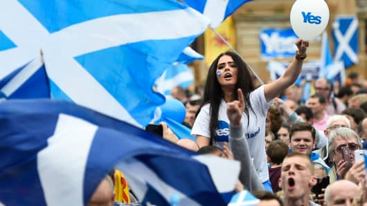 "Campaigners wave Scottish Saltires at a ""Yes"" campaign rally in Glasgow, Scotland, Sept. 17, 2014."
