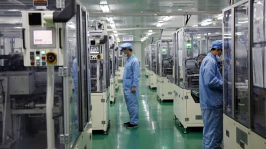 Workers operate on the vehicle battery assembly area of Wanxiang Group's electric automobile division in Hangzhou, Zhejiang province, China.