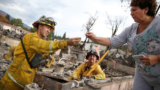 Redding, Calif., firefighters help a resident search for personal belongings in the remains of her destroyed home in Weed, Calif., Sept. 16, 2014.