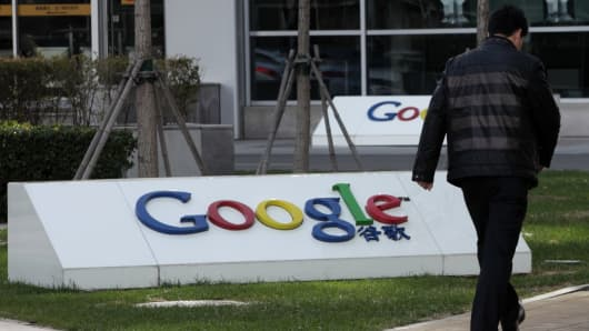 A pedestrian walks past the Google Inc. logo displayed outside the building housing the company's China headquarters in Beijing, China.