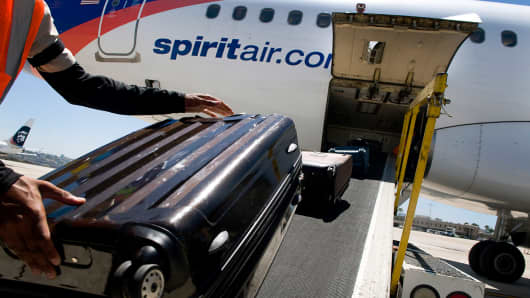 A ground crew member loads baggage onto a Spirit Airlines plane at the San Diego International Airport.
