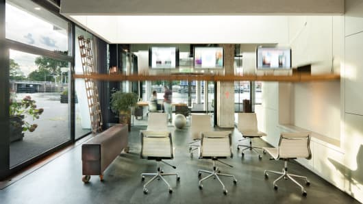 At 6pm, desks are lifted into the ceiling using a key-operated lifting mechanism and steel ceiling cables.