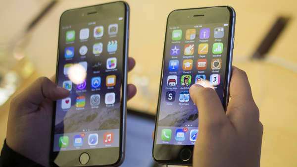A customer holds an iPhone 6 Plus, left, and an iPhone 6 after the phones went on sale at the Fifth Avenue Apple store in New York, Sept. 19, 2014.