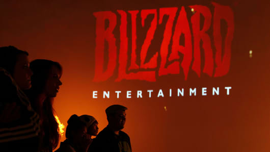 Attendees stand in front of the logo for Blizzard Entertainment as they watch a trailer for the company's Diablo III video game during the E3 Electronic Entertainment Expo in Los Angeles